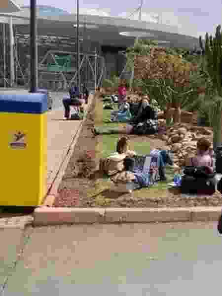 Turistas expulsos de hotéis se acumulam no gramado do lado de fora aeroporto - Reprodução - Reprodução