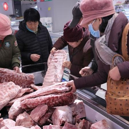 Consumidores selecionam carne de porco congelada, liberada das reservas estatais, em Nantong, China - CHINA DAILY