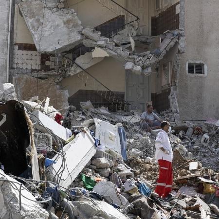 16.mai.2021 - Palestinos observam os destroços de imóveis após um ataque em Gaza - Mahmud Hams/AFP