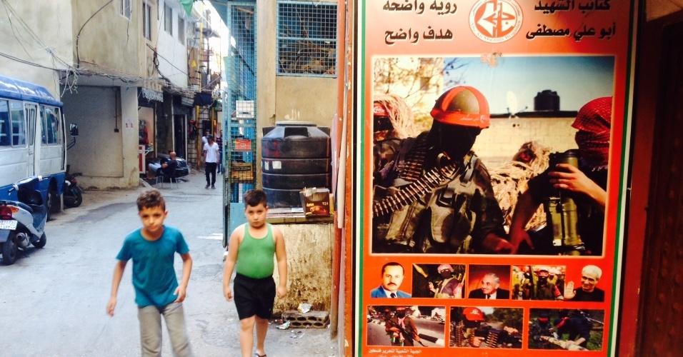 Em Chatila, no Líbano, crianças brincam ao lado de pôster que mostra combatentes armados da Frente Popular para a Libertação da Palestina