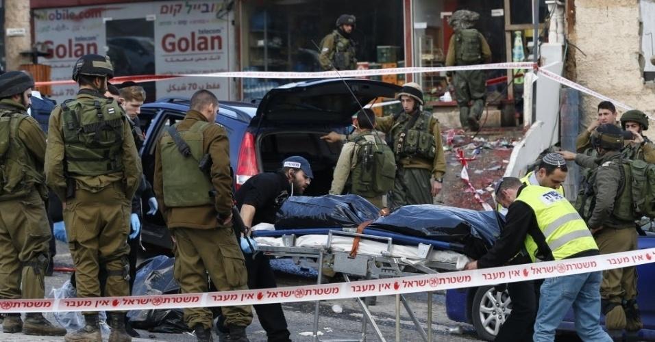3.dez.2015 - Soldados israelenses retiram o corpo de um suposto assaltante palestino que foi baleado na sequência de um ataque a um posto de controle na aldeia da Cisjordânia. Um soldado de Israel e um pedestre ficaram feridos