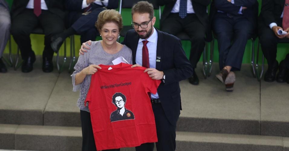 """22.mar.2016 - A presidente Dilma Rousseff posa para foto segurando uma camiseta vermelha com estampa de seu rosto e a frase """"Não vai ter golpe"""", nesta terça-feira, no Palácio do Planalto, em Brasília, durante encontro com grupo de juristas. O encontro foi articulado para demonstrar o apoio da classe jurídica ao governo da presidente"""