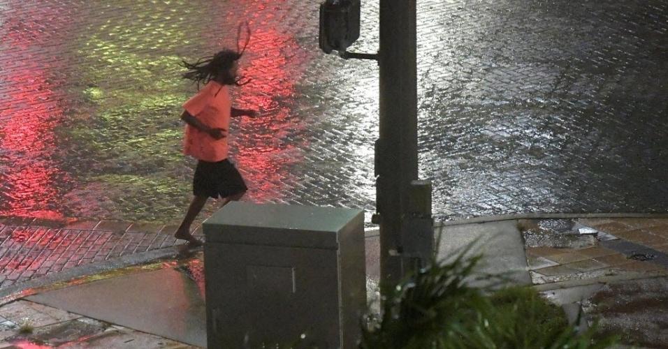 7.out.2016 - Pedestre corre em rua vazia durante a aproximação do olho do furacão Matthew em Daytona Beach, na Flórida