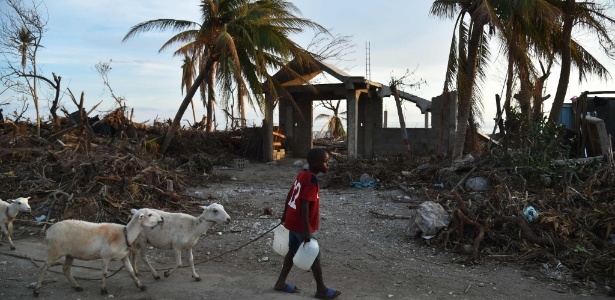 Garoto passa por casas destruídas pela passagem do furacão Matthew, em Les Cayes, Haiti