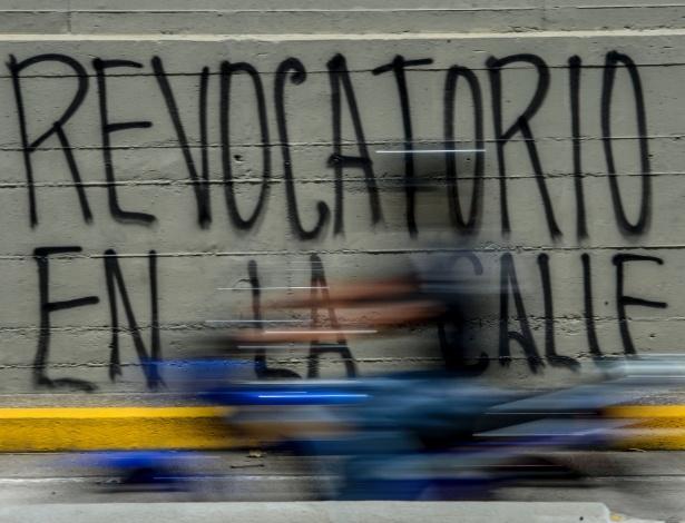 """Homem passa de moto por pichação que diz """"(o referendo) revogatório nas ruas"""", em Caracas, na Venezuela"""