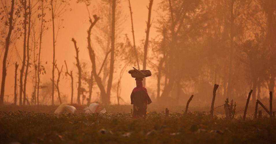 1.nov.2016 - Mulher carrega cesta na cabeça através de um campo em manhã com forte nevoeiro nos subúrbios de Srinagar, na Índia