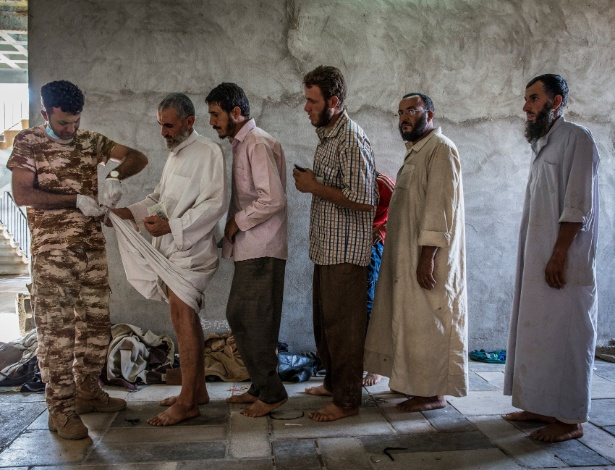 Ex-membros do Estado Islâmico são inspecionados em um centro de triagem de segurança em Kirkuk, no Iraque