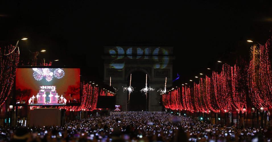 Multidão se reúne para ver a passagem do ano no Arco do Triunfo, em Paris, na avenida Champs-Elysees