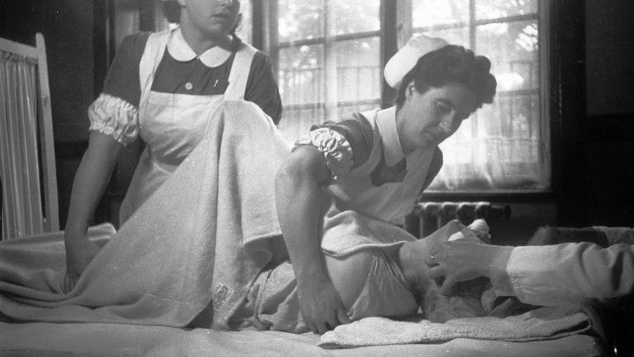 Enfermeiros atendem um paciente que recebe tratamento com eletrodo em hospital psiquiátrico, em imagem sem data - Kurt Hutton/Getty Images