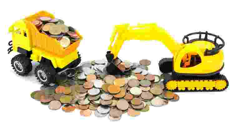 Retroescavadeira e caminhão recolhem moedas; dinheiro, imposto, IPVA - Getty Images/iStockphoto/phanasitti - Getty Images/iStockphoto/phanasitti