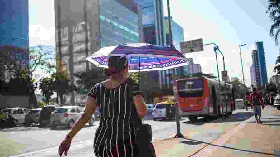 12.set.2019 - Pedestre usa sombrinha para se proteger do sol forte na Avenida Brigadeiro Faria Lima, na capital paulista - TIAGO QUEIROZ/ESTADÃO CONTEÚDO