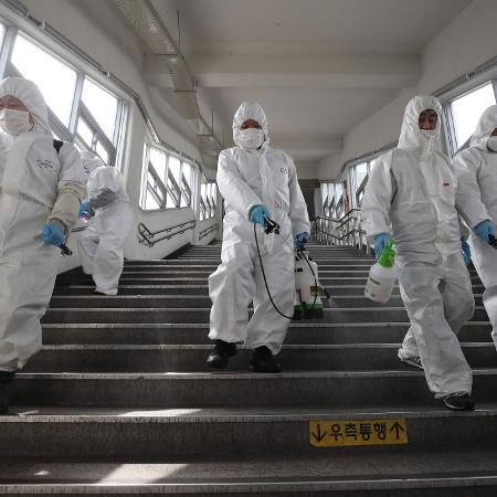 Funcionários desinfetam uma estação de metrô em Seul, na Coreia do Sul, em uma ação para evitar o aumento de transmissões do novo coronavírus no país - YONHAP / AFP