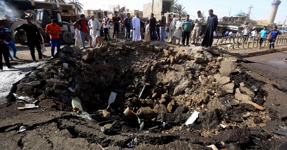 18.jul.2015 - Iraquianos observam neste sábado (18) a cratera deixada por um atentado com carro-bomba realizado no dia anterior pelo grupo terrorista Estado Islâmico na cidade predominantemente xiita de Khan Bani Saad, 20 km ao norte de Bagdá. O ataque suicida do grupo terrorista de maioria sunita matou ao menos 97 pessoas em pleno feriado do Eid al-Fitr, se tornando um dos mais mortíferos desde que ocupou partes do norte e oeste do Iraque