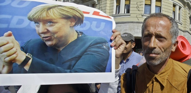 Refugiada segura pôster da chanceler alemã, Angela Merkel, enquanto grupo deixa Budapeste em direção à fronteira com a Áustria