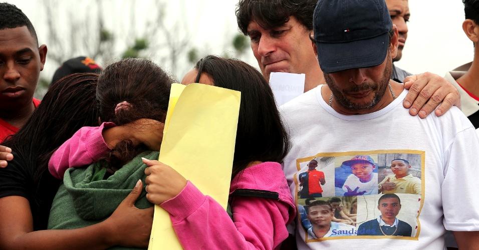 30.nov.2015 - Parentes dos jovens assassinados por PMs no Rio de Janeiro prestam últimas homenagens às vítimas durante o enterro, no cemitério de Irajá, zona norte da capital fluminense. O veículo onde os rapazes estavam foi atingido por mais de 50 tiros de fuzil