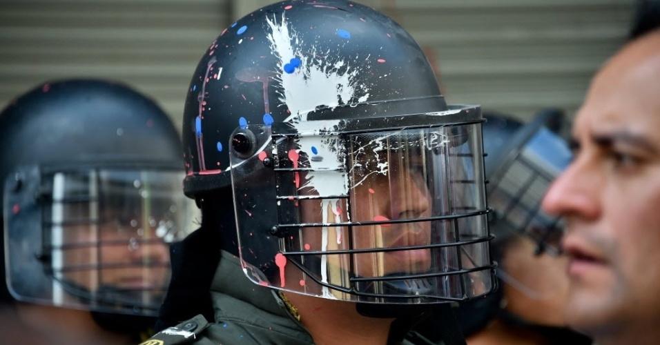 17.mar.2016 - Um policial tem o capacete manchado com tinta durante um protesto organizado pelos sindicatos contra as políticas econômicas e sociais do presidente Juan Manuel Santos, em Bogotá, Colômbia