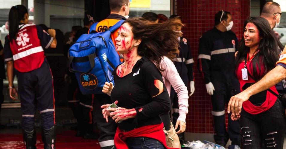 7.mai.2016 - Mulher com tinta vermelha simulando sangue corre em frente à estação Butantã do metrô, na zona oeste de São Paulo. O local recebeu um treinamento de combate ao terrorismo. Participam da simulação equipes da Polícia Civil, o Corpo de Bombeiros e o Samu (Serviço de Atendimento Movél de Urgência)
