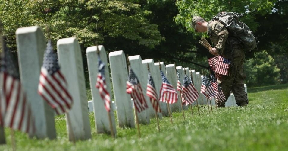 26.mai.2016 - Soldado coloca uma bandeira em cada lápide do cemitério na Virginia durante o Memorial Day, data escolhida para homenagear os militares americanos que morreram em combate