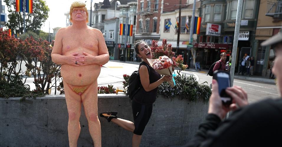 18.ago.2016 - Jovem posa para foto ao lado da estátua de Donald Trump, em San Francisco, EUA
