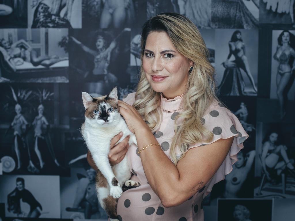 A empresária Maísa Pacheco, dona do Vênus Sex Shop, e a gata Bardot, que foi resgatada da rua e mora na loja há 3 meses