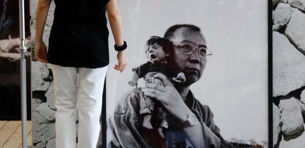 Retrato de Liu Xiaobo segurando um boneco durante exposição em Hong Kong em 2012