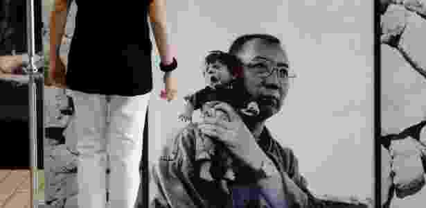Retrato de Liu Xiaobo segurando um boneco durante exposição em Hong Kong em 2012 - Bobby Yip/ Reuters