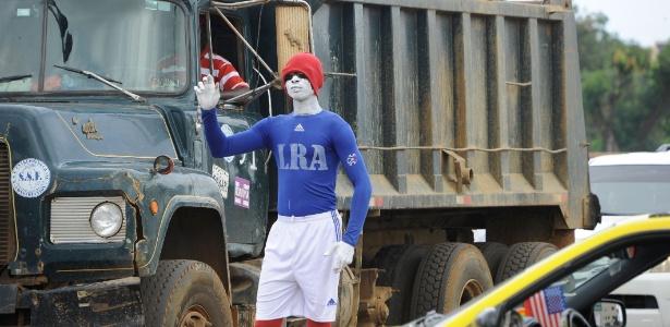 Joseph Yarkpawolo se exibe no trânsito com o corpo pintado, em Monróvia