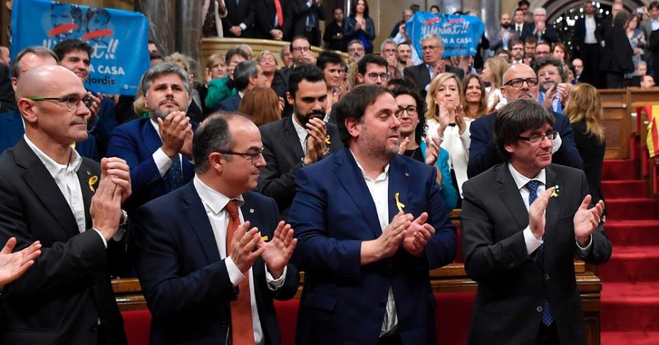 Presidente da Catalunha, Carles Puigdemont (direita) e os integrantes de seu gabinete, Oriol Junqueras (segundo à direita), Jordi Turull (terceiro) e Raul Romeva (esquerda), aplaudem a declaração de independência pelo Parlamento Catalão
