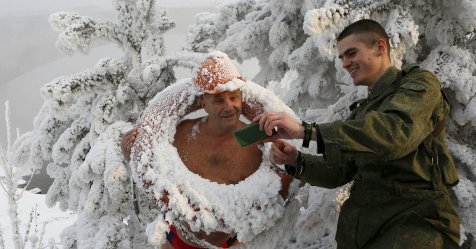 """6.jan.2015 - Mikhail Sashko, líder do clube siberiano de natação de inverno, olha foto tirada por Mikhail Shakov (dir.). """"Minha mulher diz que eu sou louco"""", diz Sashko"""