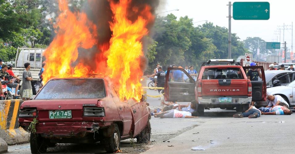 """30.jul.2016 - Carro é incendiado e """"vítimas"""" esperam por atendimento em estrada durante treinamento contra terremotos em Taguig, na região metropolitana de Manila. O exercício é conduzido pelo Comando da Reserva das Forças Armadas das Filipinas, com o auxílio de algumas agências governamentais"""