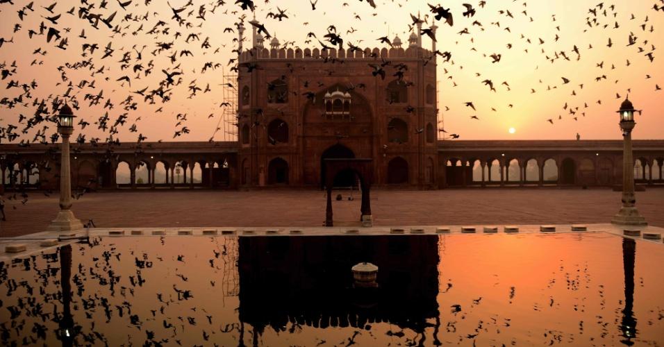 27.out.2016 - Pássaros voam sobre a mesquita Jama Masjid enquanto o sol nasce na cidade de Nova Délhi, na Índia