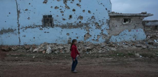 Garota caminha diante de casa destruída em al-Rai, cidade ao norte de Aleppo, na Síria