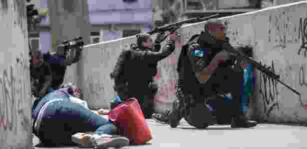 22.set.2017 - PMs e jornalistas se refugiam durante tiroteio na passarela que dá acesso à Rocinha - Mauro Pimentel/AFP