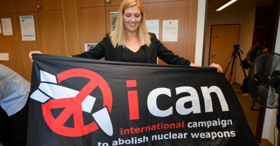 6.out.2017 - Beatrice Fihn, diretora-executiva do Ican, segura faixa com logo da campanha após anúncio do Prêmio Nobel da Paz