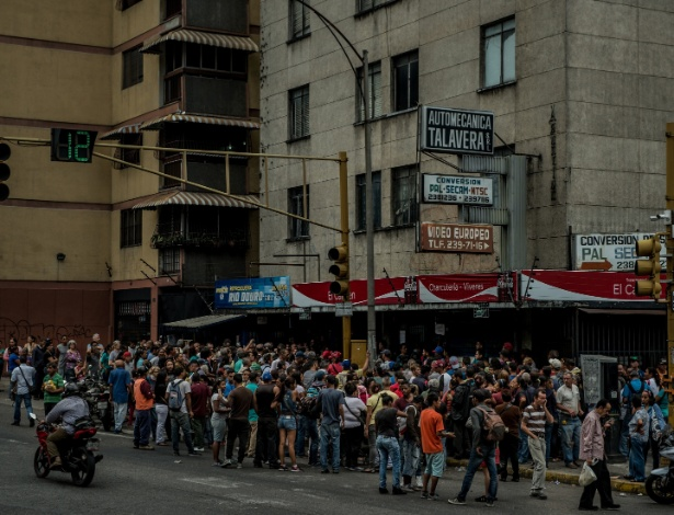 Pessoas formam fila fora de um mercado que teve rumores de ter recebido um carregamento de farinha de milho, um produto alimentício altamente procurado na Venezuela