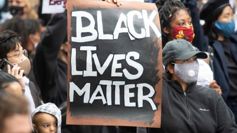 Manifestante segura cartaz com dizeres Black Lives Matter - picture alliance/dpa/picture alliance via Getty I