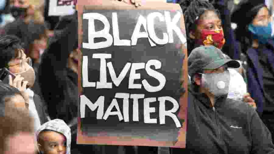 "Manifestante segura cartaz com dizeres ""Black Lives Matter"" (vidas negras importam) durante protesto nos EUA - picture alliance/dpa/picture alliance via Getty I"