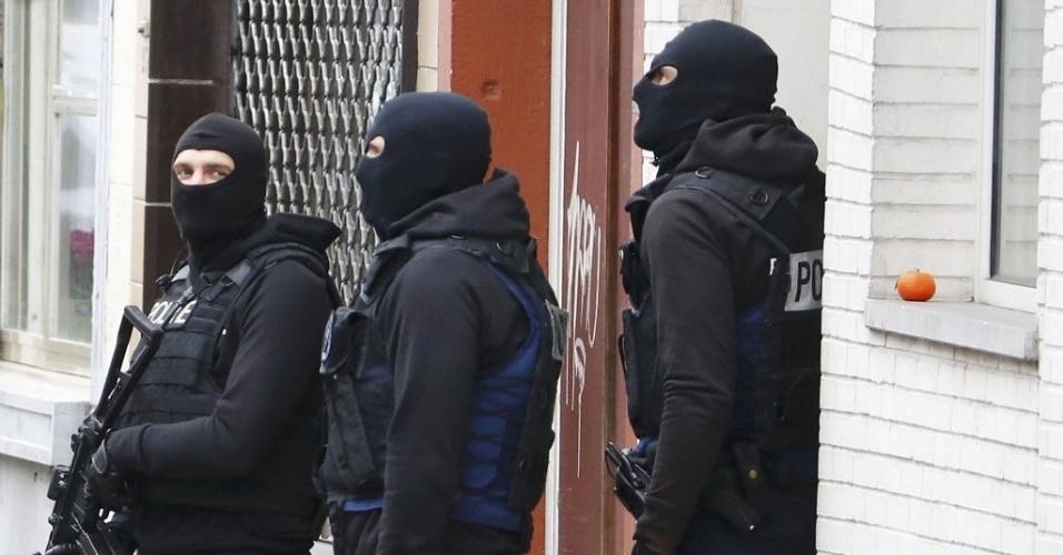 16.nov.2016 - Policiais belgas fortemente armados realizam operação em Molenbeek, bairro de Bruxelas, para tentar prender suspeitos de ataques terroristas em Paris