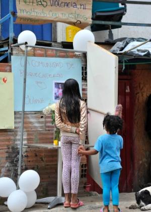 Meninas observam a casa de Yuliana Andrea Samboni, 7, estuprada e morta em Bogotá, na Colômbia