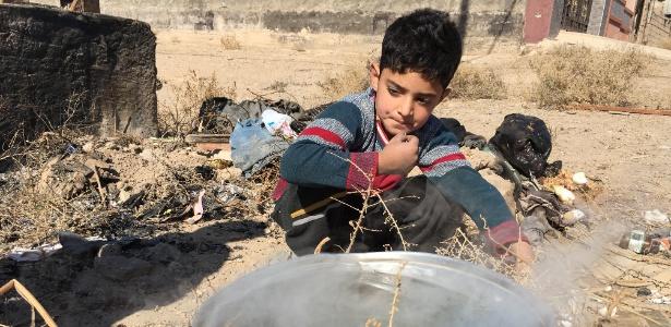 Ubaida, 6, aquece água em uma fogueira em Fallujah, no Iraque