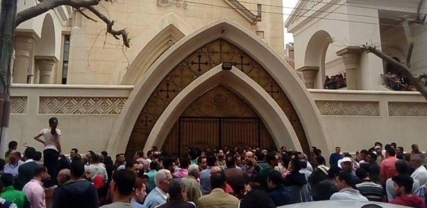 Pessoas buscam informações na entrada da igreja em Tanta, local da explosão deste domingo