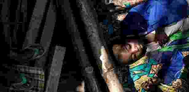 7.jun.2017 - Menino deitado enquanto aguarda comida em centro para desabrigados na região de Kasai (República Democrática do Congo); país sofre com guerra civil e racionamento de comida - AFP PHOTO / JOHN WESSELS - AFP PHOTO / JOHN WESSELS