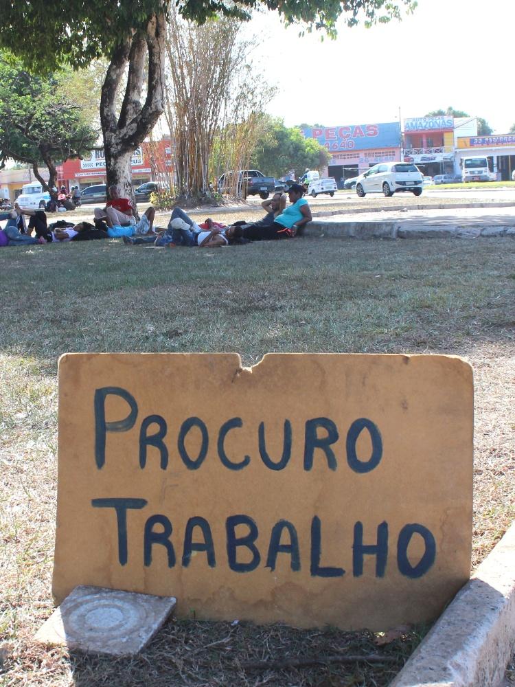 Placa com pedido de emprego na Praça Simón Bolívar, onde venezuelanos estão vivendo em Boa Vista