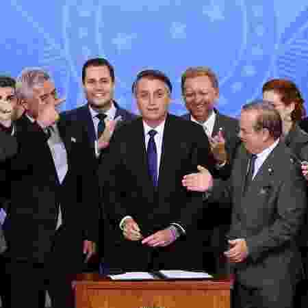 7.mai.2019 - O presidente Jair Bolsonaro cercado por parlamentares em cerimônia de assinatura do decreto sobre armas - Evaristo Sa/AFP