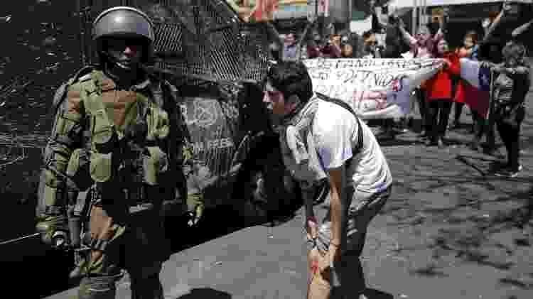 Manifestante mostra ferimento de bala de borracha para militar em Valparaíso - Javier Torres / AFP
