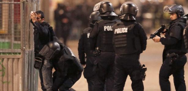 18.nov.2015 - Policiais revistam morador durante operação na região de Saint-Denis, no norte de Paris
