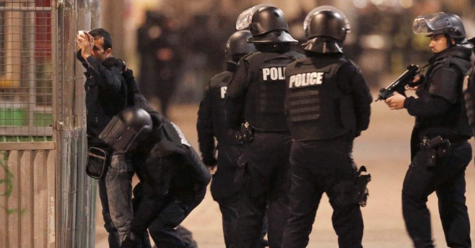 18.nov.2015 - Policiais revistam morador durante operação na região de Saint-Denis, no norte de Paris. A polícia está realizando uma grande operação para tentar localizar suspeitos de ligação com os atentados que deixaram pelo menos 129 mortos na última sexta-feira (13). Testemunhas relataram intenso tiroteio no local