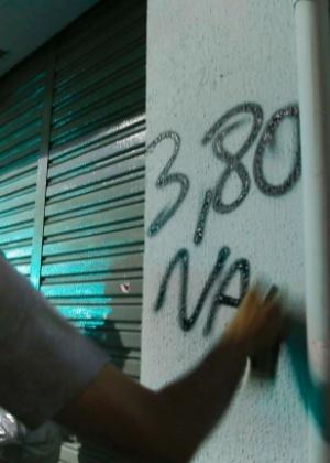 """Jovem com o rosto coberto picha """"3,80 não"""" em parede de comércio no centro de São Paulo"""