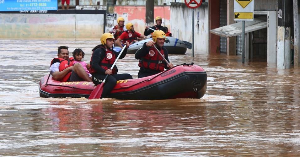 11.mar.2016 - Bombeiros usam bote para resgatar pessoas que ficaram ilhadas em alagamento em Itapevi, na Grande São Paulo