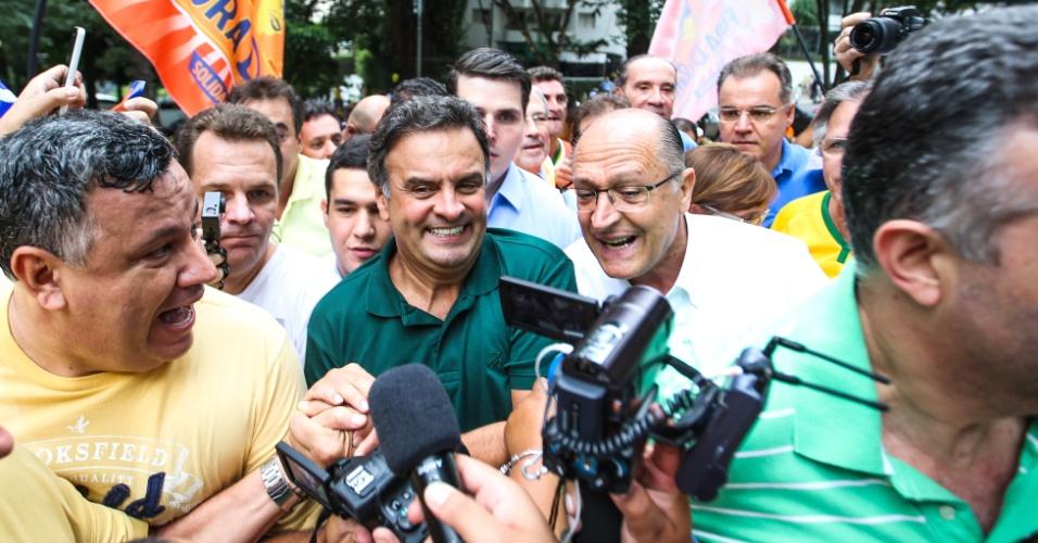 13.mar.2016 - O governador de São Paulo, Geraldo Alckmin (à dir), e o senador Aécio Neves (PSDB) (à esq.) foram hostilizados e aplaudidos em rápida passagem pelo ato contra o governo Dilma Rousseff na avenida Paulista, região central de São Paulo